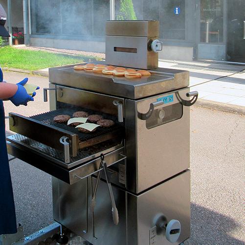 Metos Burger Machine -puuhiiliuuni, hampurilaissämpylät ja -pihvit paistumassa.