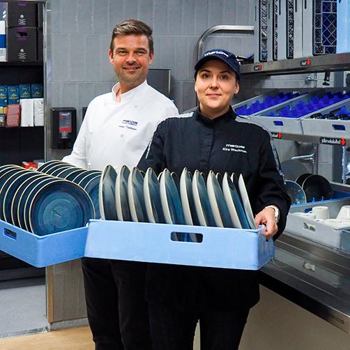 Kouluttaja Kira Weckman ja keityspäällikkö Janne Tirkkonen esittelevät lautaskoreja Metos-astianpesuosastolla