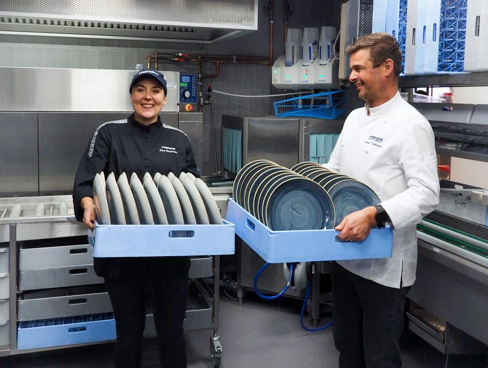 Kouluttaja Kira Weckman ja keityspäällikkö Janne Tirkkonen esittelevät lautaskoreja astianpesuosastolla